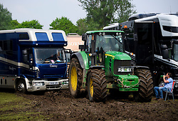 © London News Pictures. 12/05/2016. Windsor, UK. Vehicles being removed from heavy mud by tractors on the first day of the 2016 Royal Windsor Horse Show, held in the grounds of Windsor Castle in Berkshire, England. The opening day of the event was cancelled due to heavy rain and waterlogged grounds. This years event is part of HRH Queen Elizabeth II's 90th birthday celebrations.  Photo credit: Ben Cawthra/LNP