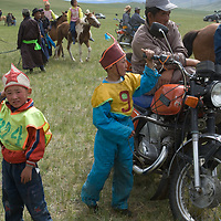 Young, costumed, bareback riders with older relatives after a 20km race at a traditional naadam festival on a remote pass in Arbulag Sum, near Muren in Hovsgol Aimag, Mongolia. The motorcycle is a sign of rapid changes in their nomadic lifestyle.