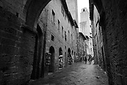Street scene with a tower in the distance, San Gimignano, Tuscany, Italy. (Also available in full color).