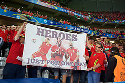 """LILLE, FRANCE - Friday, July 1, 2016: Wales supporters with a banner """"Heroes just for one day"""" celebrate the 3-1 victory against Belgium at full time after the UEFA Euro 2016 Championship Quarter-Final match at the Stade Pierre Mauroy. Aaron Ramsey, Gareth Bale, captain Ashley Williams. (Pic by Paul Greenwood/Propaganda)"""