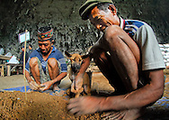 """Manggarai workers -- and their dog -- sift sediments from a Liang Bua excavation pit in search of tiny remains at the discovery site of Homo floresiensis. the Flores """"hobbit"""""""