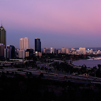 Australia, Western Australia, The full moon rises behind the Perth city skyline during evening twilight, seen from Queen Victoria Park