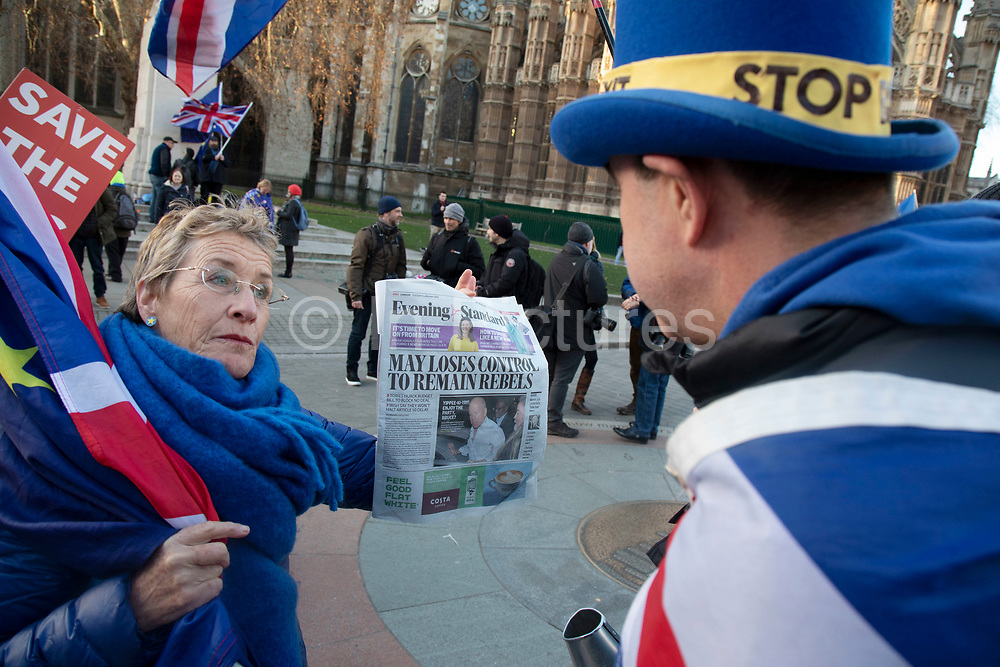 Anti Brexit pro Europe demonstrators look at an Evening Standard headline announcing that Tory rebels have put a potential block on a No Deal Brexit in Westminster opposite Parliament one week before MPs vote on the finalised deal on 8th January 2019 in London, England, United Kingdom. MPs will vote on Theresa Mays Brexit deal on Tuesday, 15 January, government sources confirmed.