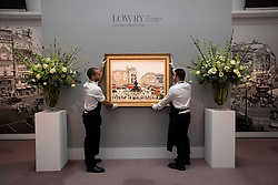 """© Licensed to London News Pictures. 21/03/2014. London, UK. Sotheby's auction house staff adjust """"Piccadilly Circus London"""" (1960) (est. GB£4,000,000-6,000,000) by British artist LS Lowry during the press view for a new sale of the artist's work in London today (21/03/2014). The auction, entitled """"Lowry: The AJ Thompson Collection"""", features works by Lowry assembled over a 30 year period by collector A.J. Thompson. Photo credit: Matt Cetti-Roberts/LNP"""