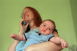Teenage mother holding baby and talking on the telephone,