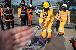 Harefield, UK. 12th September, 2020. A security guard working on behalf of HS2 obstructs the photographer's camera as his colleagues forcibly remove environmental activists acting in solidarity with HS2 Rebellion from the road in front of a gate providing access to a site for the HS2 high-speed rail link. Anti-HS2 activists continue to try to prevent or delay works on the controversial £106bn HS2 high-speed rail link in the Colne Valley where thousands of trees have already been felled.
