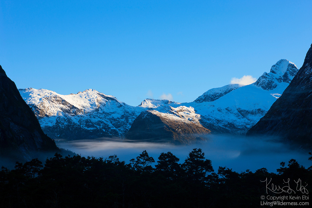 Several peaks of the Darran Mountains are visible above the fog and Gertrude Valley in Fiordland National Park, New Zealand. The two primary summits in this image are Barrier Knob, a 1,879-meter-tall (6,165-foot) summit on the left; and Barrier Peak, a 2,039-meter (6,690-foot) summit on the right. Located on the southwestern portion of the South Island, Fiordland National Park is New Zealand's largest national park.