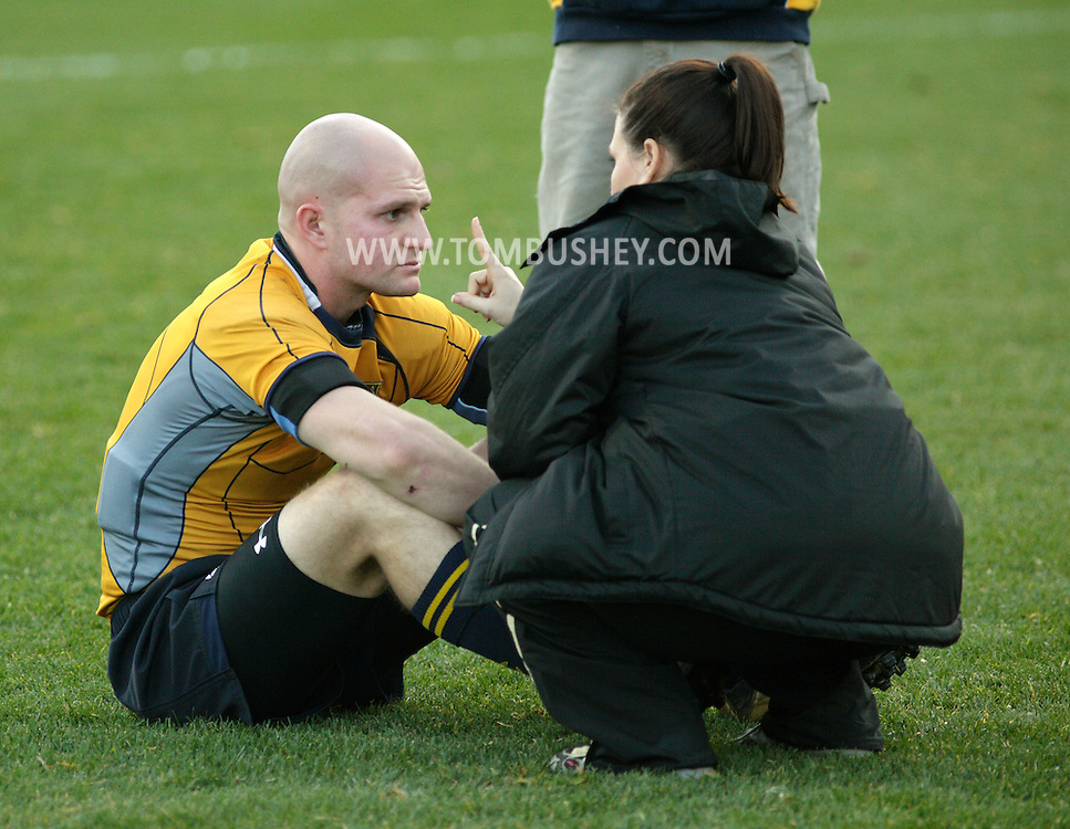 West Point, NY - An athletic trainer checks on an injured Navy player during a rugby match against Army at the Anderson Rugby Center at the United State Military Academy on Nov. 21, 2009. ©Tom Bushey / The Image Works
