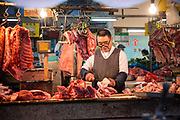 A butcher carves up cuts of meat at his stall at a fresh food market in Shanghai, China, on Saturday, Dec. 5, 2015.