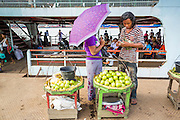 """17 JUNE 2013 - YANGON, MYANMAR:  A fruit vendor watches a Yangon bound ferry pull away from the dock in Dala. The ferry to Dala opposite Yangon on the Yangon River is the main form of transportation across the river. Every day the ferry moves tens of thousands of people across the river. Many working class Burmese live in Dala and work in Yangon. The ferry is also popular with tourists who want to experience the """"real"""" Myanmar. The rides takes about 15 minutes. Burmese pay about the equivalent of .06¢ US for a ticket.  Foreigners pay about the equivalent of about $4.50 US for the same ticket.   PHOTO BY JACK KURTZ"""