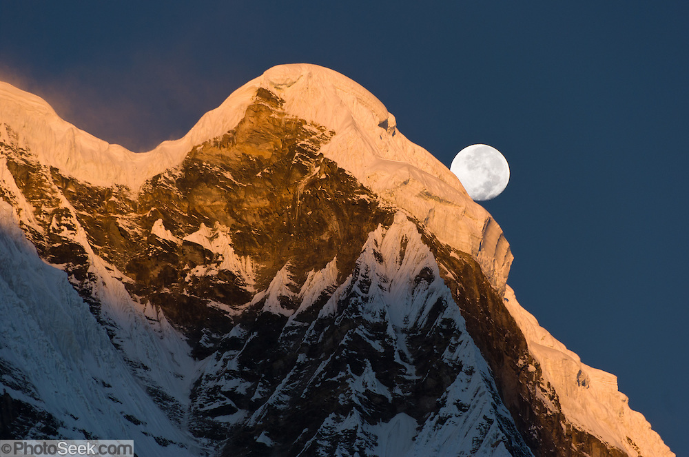 """The moon sets at sunrise over Annapurna South, seen from Annapurna South Base Camp (ABC, at 13,550 feet elevation), in the Himalaya mountain range of Nepal. Annapurna South (also known as Annapurna Dakshin, or Moditse; 23,684 feet / 7219 meters) was first climbed in 1964 by a Japanese expedition. Annapurna is Sanskrit for """"Goddess of the Harvests."""" In Hinduism, Annapurna is a goddess of fertility and agriculture and an avatar of Durga. Published in """"Light Travel: Photography on the Go"""" book by Tom Dempsey 2009, 2010."""