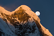 "The moon sets at sunrise over Annapurna South, seen from Annapurna South Base Camp (ABC, at 13,550 feet elevation), in the Himalaya mountain range of Nepal. Annapurna South (also known as Annapurna Dakshin, or Moditse; 23,684 feet / 7219 meters) was first climbed in 1964 by a Japanese expedition. Annapurna is Sanskrit for ""Goddess of the Harvests."" In Hinduism, Annapurna is a goddess of fertility and agriculture and an avatar of Durga. Published in ""Light Travel: Photography on the Go"" book by Tom Dempsey 2009, 2010."