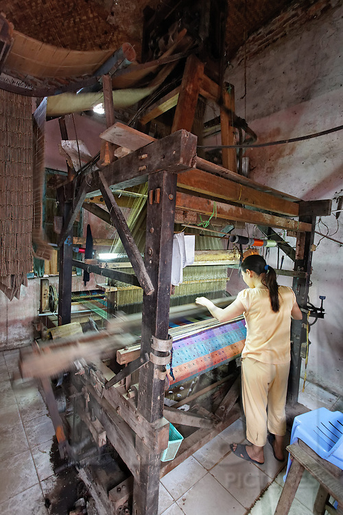 A craftswoman makes complex colored patterns with her jacquard loom in Van Phuc silk village, Hanoi, Vietnam, Southeast Asia