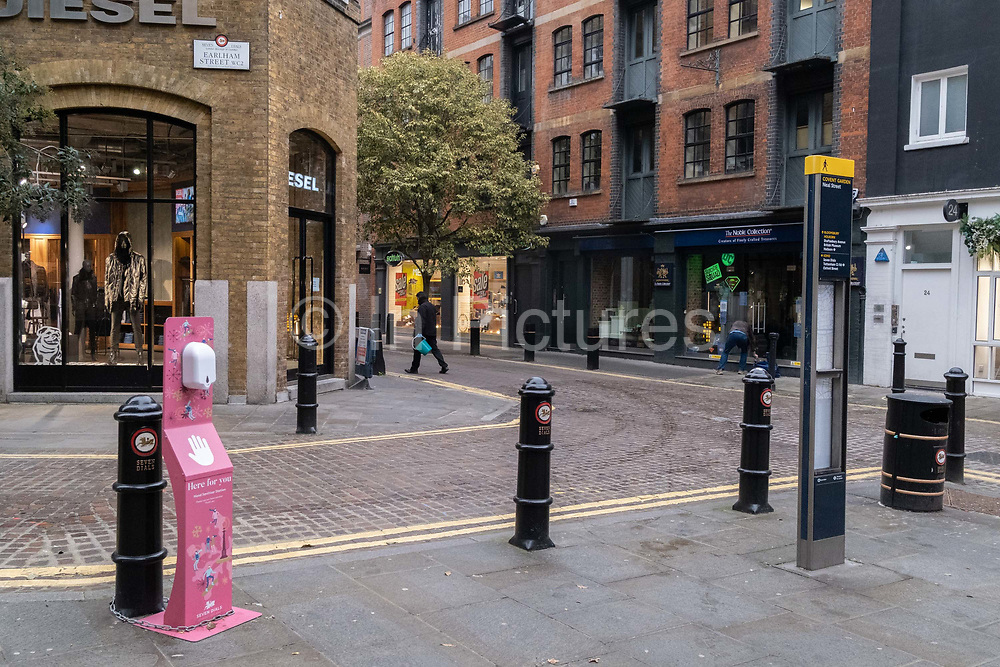 With non-essential shops still closed, a sanitiser dispenser remains unused on the quiet corner of Earlham and Neal Streets near Covent Garden, during the third lockdown of the Coronavirus pandemic, on 22 February 2021, in London, England.