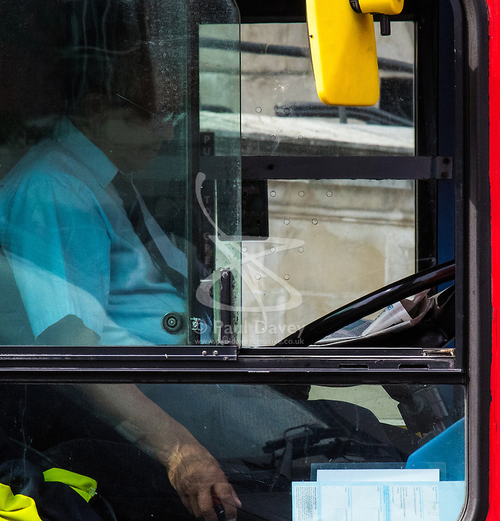 London, June 18th 2015. A London bus driver reads the Evening Standard whilst negotiating the heavy, slow-moving traffic near St Paul's Cathedral, seemingly untroubled about the safety of the many pedestrians, his passengers and other road users. /// Contact/Payment details: Paul@pauldaveycreative.co.uk Tel: 07966016296