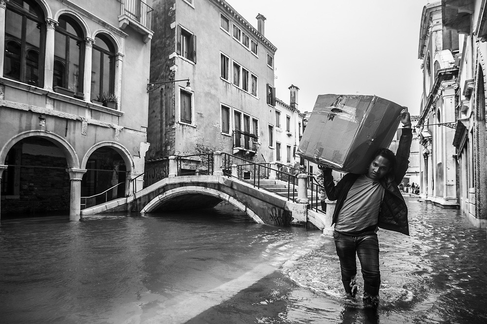 Venice, Italy. 29 October, 2018. A worker carries his goods during the high tide in Cannaregio district on October 29, 2018, in Venice, Italy. This is a selection of pictures of different areas of Venice that the press has not covered, were resident live and every year they have to struggle with the high tide. Due to the exceptional level of the 'acqua alta' or 'High Tide' that reached 156 cm today, Venetian schools and hospitals were closed by the authorities, and citizens were advised against leaving their homes. This level of High Tide has been reached in 1979. © Simone Padovani / Awakening / Alamy Live News