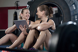 Two women relaxing and using digital tablet after exercise, Bavaria, Germany