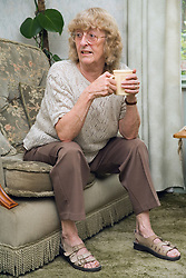Woman sitting on the sofa with a mug of coffee,