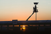 An airport employee fixes an outdoor light fixture at Boise International Airport in Boise, Idaho as the sun sets on September 11, 2007.