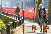 A woman is seen walking her dogs nearby Bermondsey underground station in London, Thursday, March 26, 2020. The British Government announced Tuesday, that the ExCel Center in east London will become a 4,000 bed temporary hospital to deal with future coronavirus patients, to be called NHS Nightingale. (Photo/Vudi Xhymshiti)