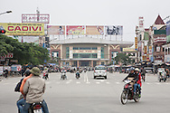 Cityscape in Vinh, Vietnam, Asia. Motorbikes and cars ride an arterial street.