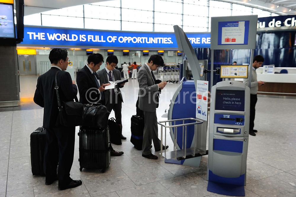 Men check in at Terminal five at Heathrow Airport.