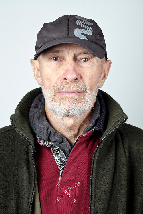 front view portrait 70 year of age person wearing a baseball cap
