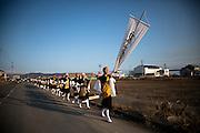 Ishinomaki - Minami Hamacho  Procession bouddhiste - 11 Mars 2012 .La cérémonie est une longue procession rythmée par les chants et les tambours. Depuis le temple proche du centre ville, les bonzes longent la rivière Kyu-Kitakami. Le premier arrêt est  sur les quais pour y procéder à la mise a leau de parchemins sur lesquels sont inscrits les noms de victimes. Ensuite elle se poursuit vers Minami Hamacho, lun des quartiers les plus touché et ou se dresse un mémorial de fleurs et de messages.