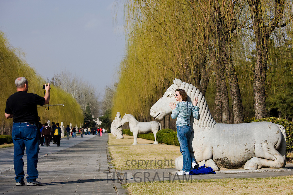 Tourist poses with statue of a resting horse, Spirit Way, Ming Tombs, Beijing (Peking), China