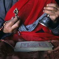 MONGOLIA, Darhad Valley. Tibetan Buddhist lama in Rinchenlhumbe with prayer book, rosary beads, a dorge (symbolic lightning bolt) & bell.