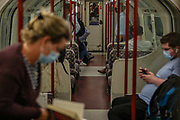 Passengers some of them wearing face protective masks preparing to leave Bakerloo Line southbound underground train in central London on Thursday, Aug 5, 2021. Met Office forecasts 26 hours of heavy rain and thunderstorms to batter the British capital. Severe thunderstorms caused flash flooding across London last Sunday afternoon, sparking major transport delays. (VX Photo/ Vudi Xhymshiti)