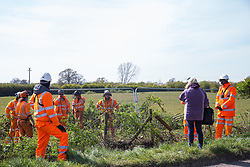 Quainton, UK. 26th April, 2021. A Stop HS2 activist monitors hedgerow clearance works during the bird nesting season for a temporary access road for the HS2 high-speed rail link. Environmental activists continue to oppose the controversial HS2 infrastructure project from a series of protection camps along its Phase 1 route between London and Birmingham.