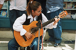 Woman playing the guitar in the street outside a bookshop at an event in Havana; Cuba celebrating World Book Day,