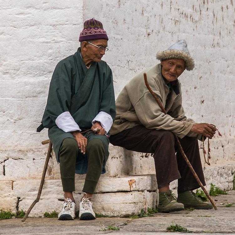 BHUTAN, PARO. Two men are chatting and seated beside a Buddhist chorten (stupa), part of the Ugyen Pelri (Royal Palace).