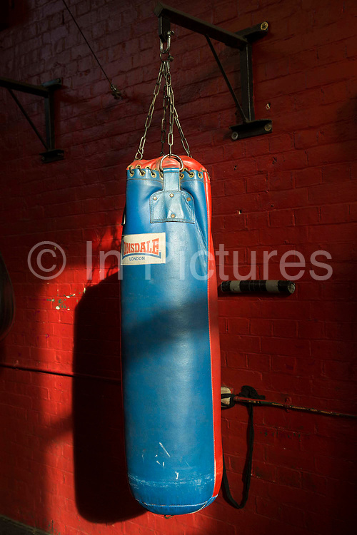 A single Lonsdale boxing punch bag hangs inside a boxing gym with red painted walls. Folkestone, Kent.