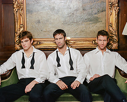 three handsome men in white shirts indoors
