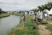 """A Manouche girl fishing near the caravans, on the edge of Saintes Maries de la Mer, during the gypsy pilgrimage<br /><br />""""Le Pelerinage des Gitans""""; the French gypsy pilgrimage of Saintes Maries de la Mer, Camargue, France<br /><br />Sainte Sara is an uncannonized saint, who legend says looked after the Christian Saints Marie Jacobe and Marie Salome, cousins of Mary Magdalene, who arrived, it is said, on the shores of the Camargue in a rudderless boat. Saint Sara is the patron saint of gypsies who come from far and wide to see her. There are even paintings of Sara as 'Kali' the black saint in Eastern Europe. Sara may have been the priestess of 'Ra' the sun-god or even servant girl to the Christian saints. No-one really knows.<br /><br />For a few weeks of the year, Roma, Gitan and Manouche gypsies come from all over Europe in May, camping in caravans around Saintes Maries de la Mer. It is a festive time where they play music, dance, party and christen their children. They all go to see Saint Sara in the crypt, kissing or touching her forehead. Many put robes on her shoulders, making her fat for the procession. In the main Gypsy procession of the 24th May, Saint Sara is allowed to leave her crypt, beneath the church, and is carried from the church to the shores of the mediterranean and back again. One day a year she is free from her prison. Hundred's of years ago the Gypsies used not even to be allowed into the church, only into the crypt like Sara...<br /><br />Roma gypsies still suffer oppressive prejudice and racism and are one of the ethnic groups the most persecuted and marginalised across Europe. The festival is one of the times where they celebrate with people of all races, their faith and traditions"""