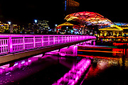 Sept. 2015 Singapore: Singapore bridge over the river at night with many colors stretched across the river.