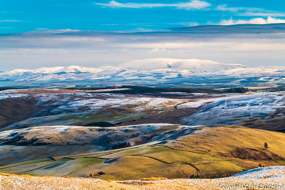 Selkirk, Scottish Borders, UK. 2nd February 2019. Looking south east from Sundhope Height (512m) at Ettrick Bridge near Selkirk to a snow covered Big Cheviot (815m) and the Anglo Scottish Border on the horizon.