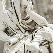 A stone statue deep in thought in front of the Konzerthaus in Gendarmenmarkt Square (Berlin, Germany).