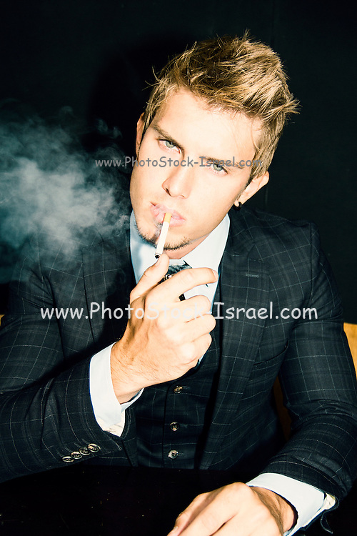 Young man in three piece suit smoking