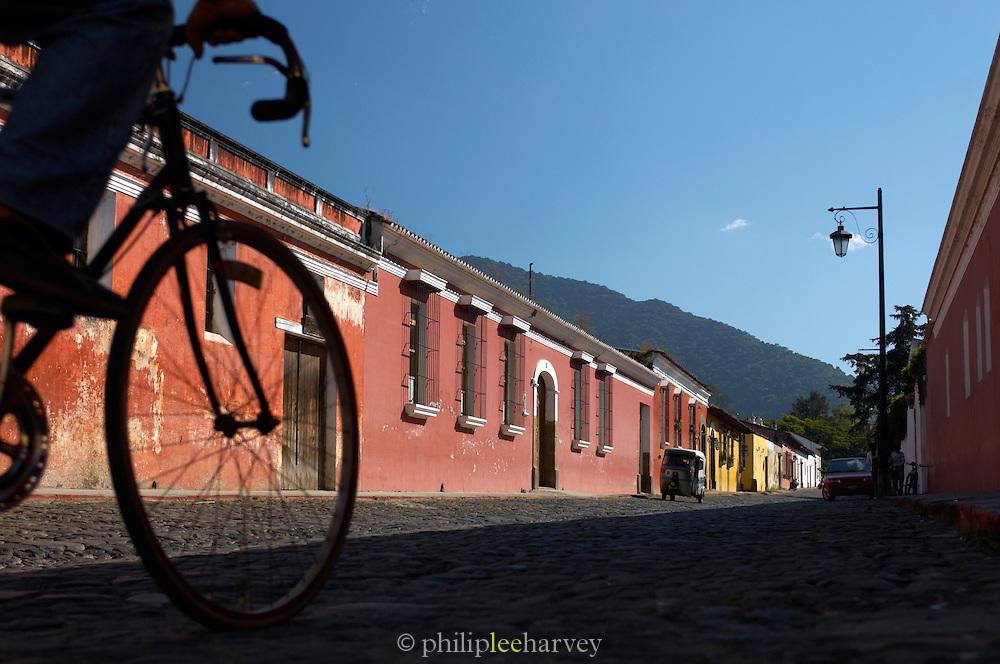Local riding a bike down a street in Antigua, a UNESCO World Heritage Site in Guatemala