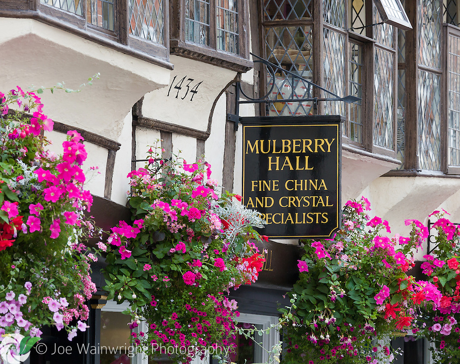 Pretty hanging baskets brighten the 15th century Mulberry Hall shop, in York.