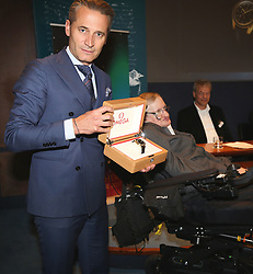 Raynald Aeschlimann, president of Omega, presenting Professor Stephen Hawking with a gold Speedmaster watch at The Royal Society in London during a press conference previewing the Starmus science and arts festival taking place in Norway next month.