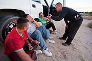 17 MAY 2006 - GILA BEND, AZ: A MCSO Deputy talks to illegal immigrants arrested in rural Maricopa county. Deputies from the Maricopa County Sheriff's Department run an anti-smuggling operation along I-8 near Gila Bend, AZ. Deputies arrested 12 illegal immigrants from Mexico during the operation. PHOTO BY JACK KURTZ