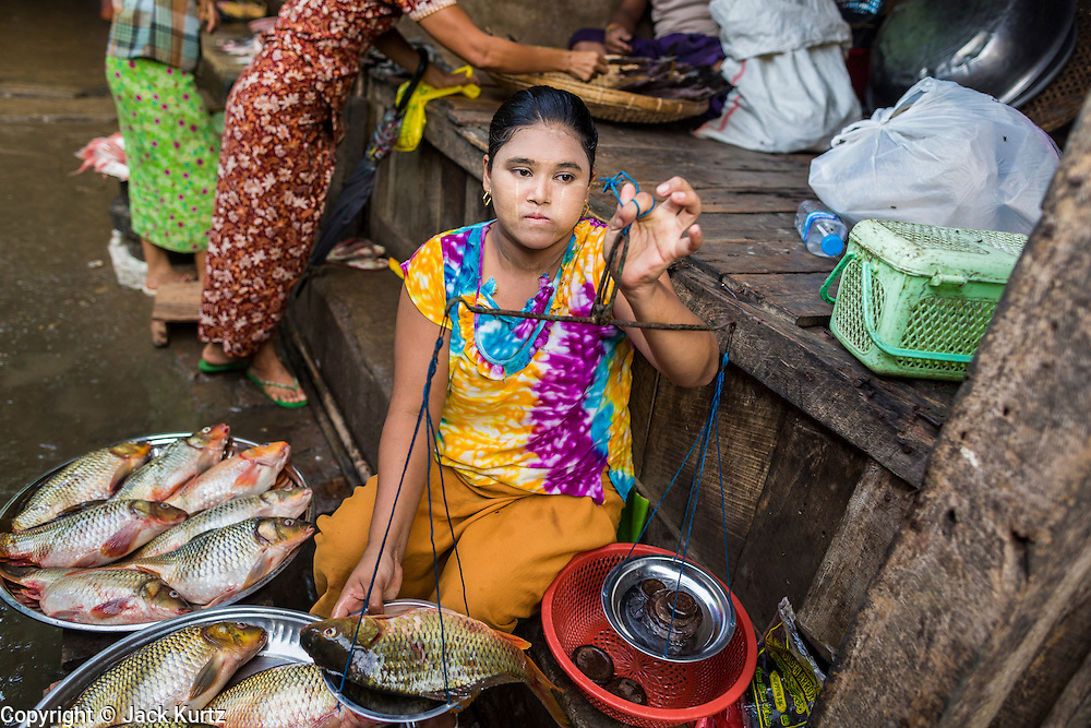 06 JUNE 2014 - IRRAWADDY DELTA,  AYEYARWADY REGION, MYANMAR:  A woman sells fish in the market in Pantanaw, a town in the Irrawaddy Delta (or Ayeyarwady Delta) in Myanmar. The region is Myanmar's largest rice producer, so its infrastructure of road transportation has been greatly developed during the 1990s and 2000s. Two thirds of the total arable land is under rice cultivation with a yield of about 2,000-2,500 kg per hectare. FIshing and aquaculture are also important economically. Because of the number of rivers and canals that crisscross the Delta, steamship service is widely available.  PHOTO BY JACK KURTZ