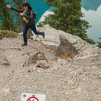 Despite signs against it, tourists wander off trails near Moraine Lake in Banff National Park, Alberta, Canada.