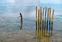July 1987, Biak, Indonesia --- A naked young boy fishes with a pointed stick near a row of wooden pilings. Biak Island, Schouten Islands, Indonesia. --- Image by © Owen Franken/CORBIS - Photograph by Owen Franken