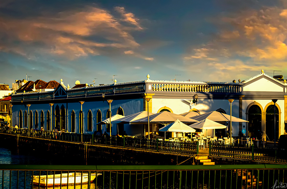 A image of the Mercado da Ribira (The Old Market Hall), on the Rio Gilão in Tavira, Portugal, with its outside restuarants, at sunset.