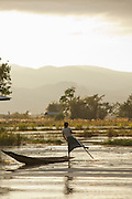 A fisherman uses the traditional way of rowing with his leg, to move through the village of Pauck Par in Inle Lake, Myanmar